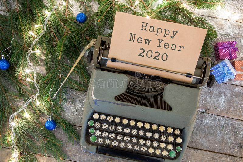 """Christmas concept - typewriter with text """"Happy New Year 2020"""", spruce branches, garland, gift boxes. On wooden background stock photos"""