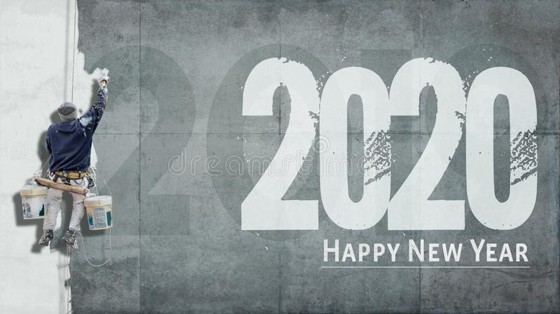 Happy New Year 2020 on facade. Building painter hanging from harness painting a wall with the words Happy New Year 2020 stock image