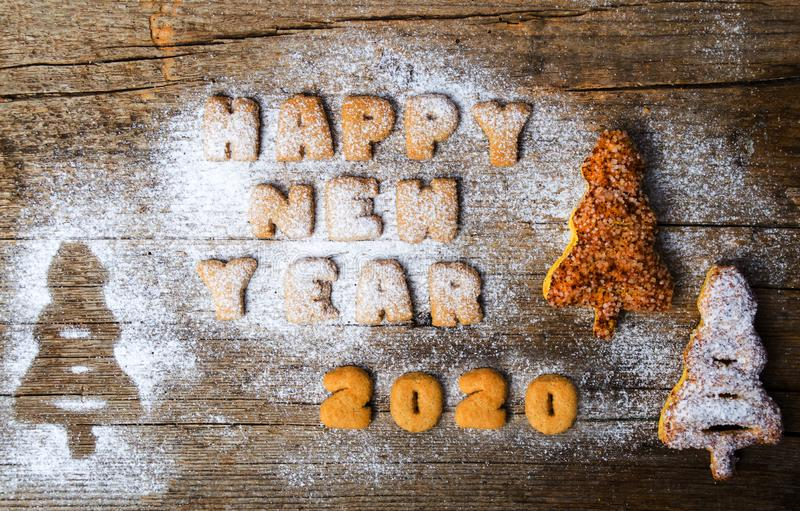 Happy new year 2020 written with cookies. Happy new year 2020 note written with cookie letters, card, biscuit, text, wooden, rustic, vintage, sugar, powder royalty free stock images