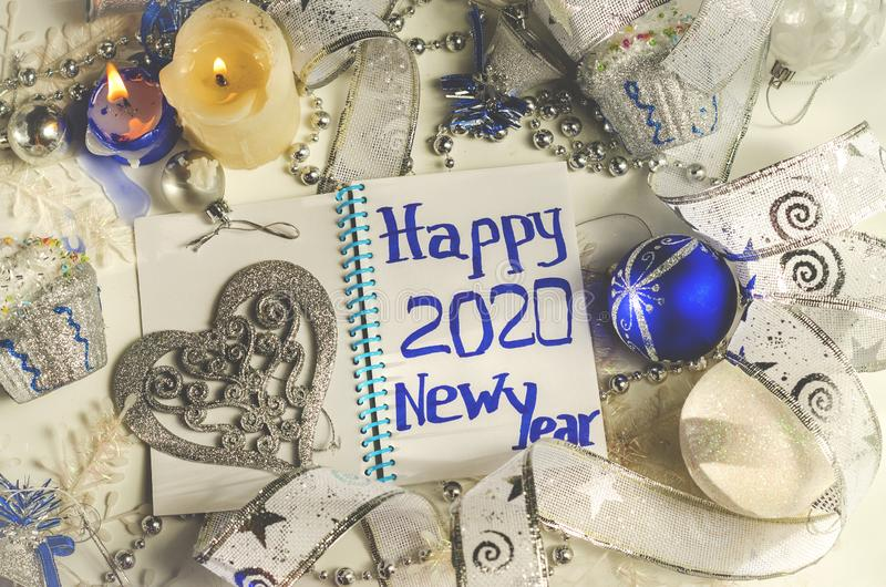 Wish happy new year 2020. In a notebook among new year decorations royalty free stock photo