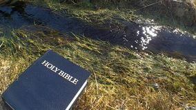 Holy Bible against a streaming water stock video